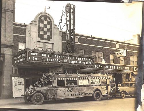 Bell's Hawaiian Revue bus in front of the Soo Theatre with original marquee